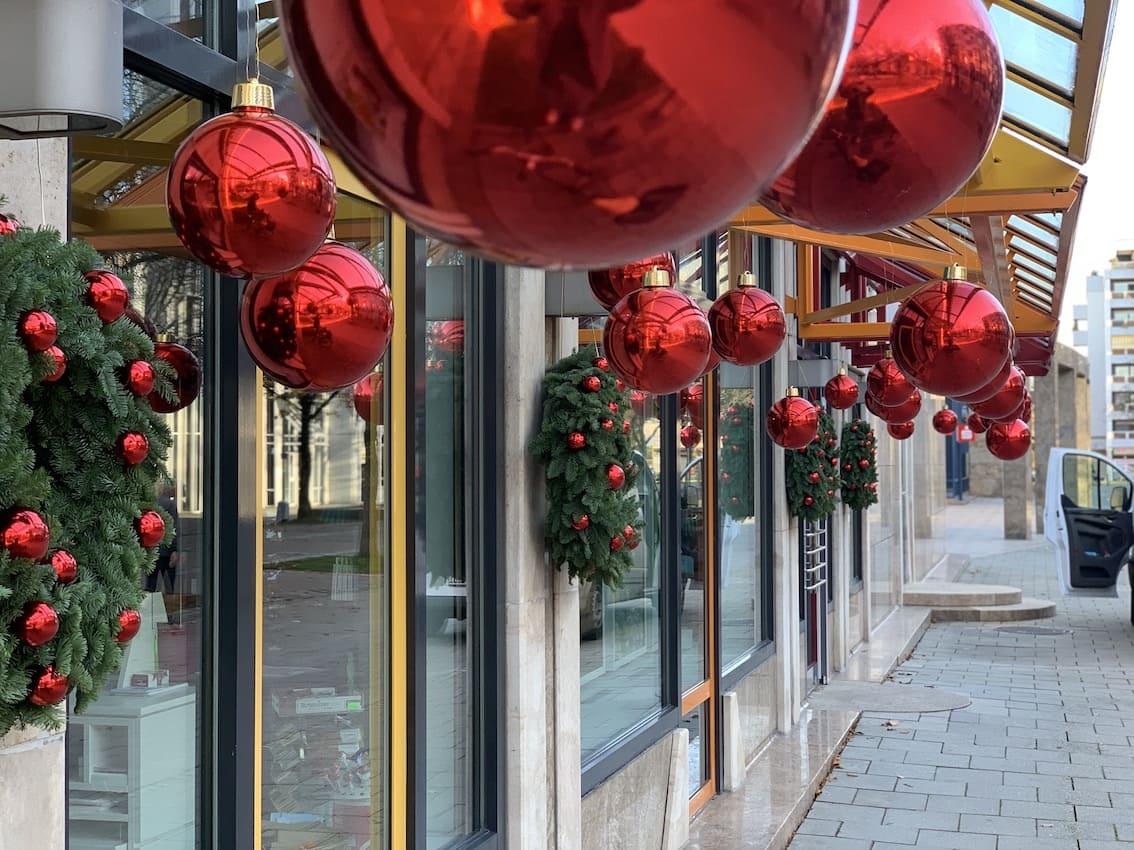 Rote Weihnachtskugeln vor Geschäft