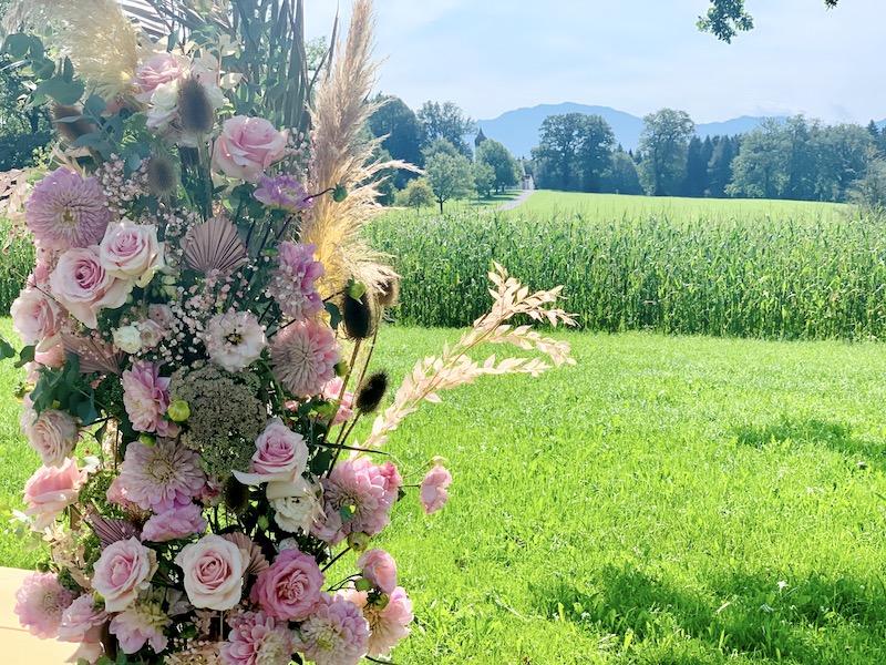 Hochzeitsbogen mit Blumen am Feld